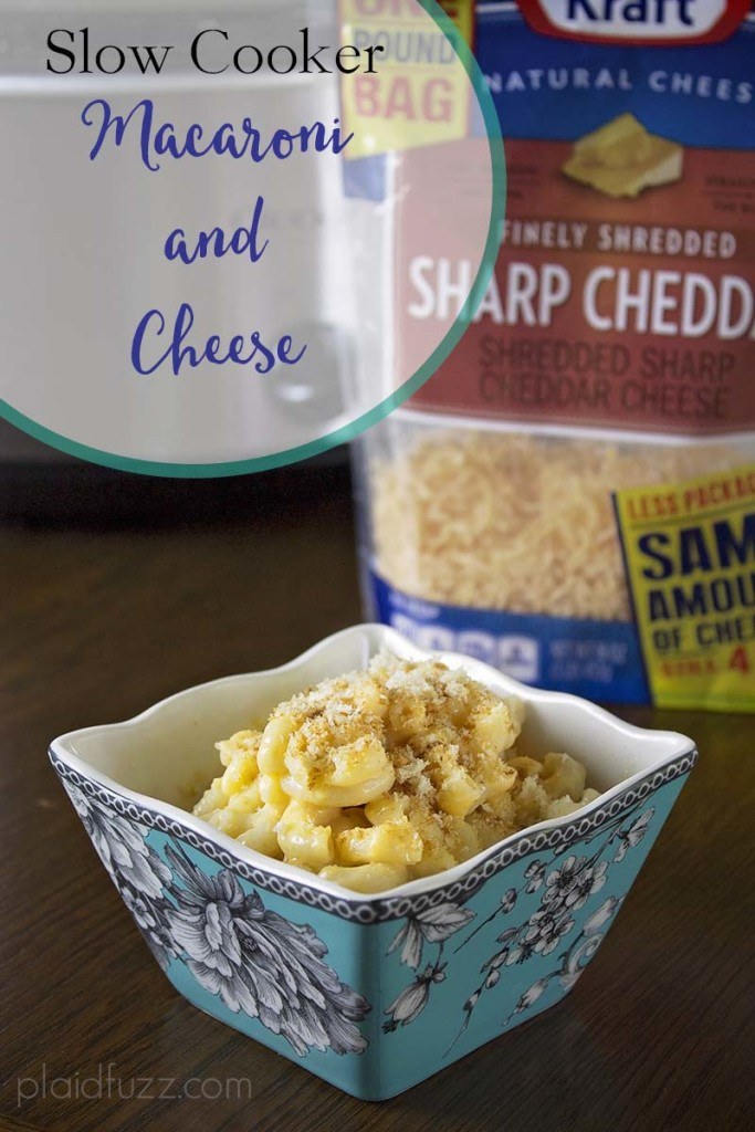 A small bowl with creamy macaroni and cheese in it with a bag of Kraft Natural Sharp Cheddar Shreds and a slow cooker in the background